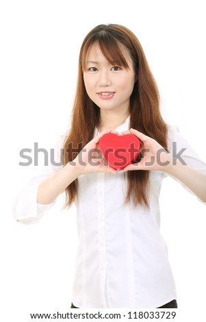 Young asian business woman shows heart symbol - stock photo