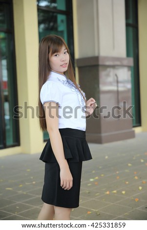 Young Asian business woman standing over office background
