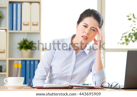 Young asian business woman with headache in office - stock photo