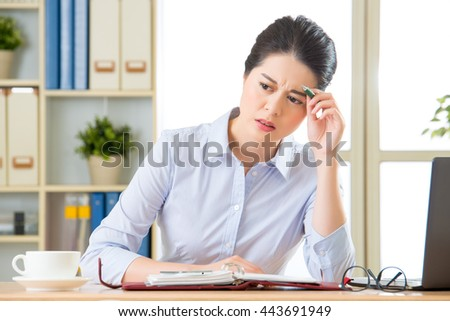 Young asian business woman writing with headache in office - stock photo