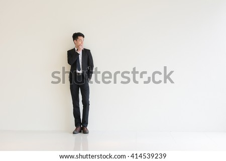 young asian businessman against the white wall - stock photo