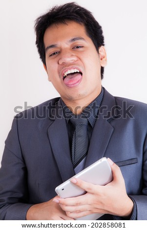 Young asian businessman bored holding a tablet