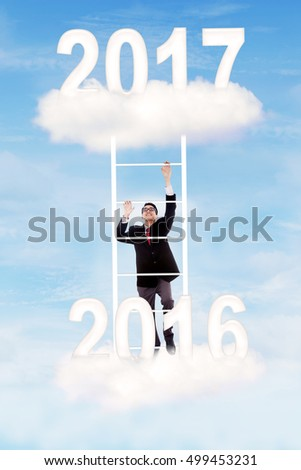 Young Asian businessman climbing a ladder toward 2017 on the cloud. Concept of business goal in 2017