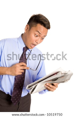 Young Asian businessman express shock as he reads the money section of newspaper