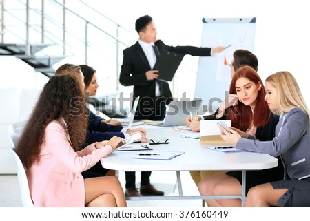 Young Asian businessman making a presentation on a board in the office