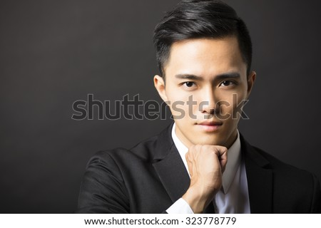 young asian businessman on black background - stock photo