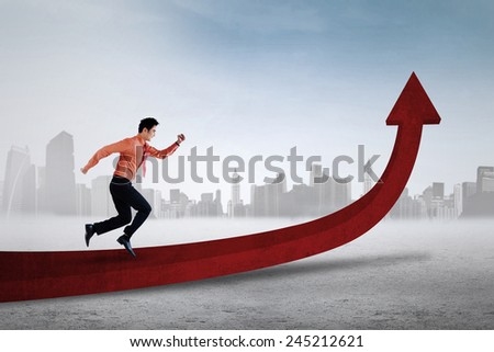 Young asian businessman running on upward red arrow, symbolizing business growth - stock photo