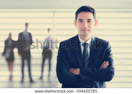 Young Asian businessman smiling while crossing his arms - leader and success businessman concepts - stock photo