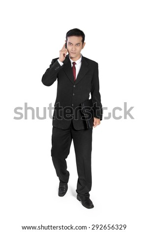 Young Asian businessman walking toward camera while making phone call, full body shot, isolated on white background