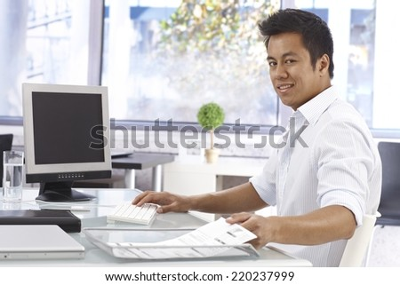 Young Asian businessman working in bright office, sitting at desk, looking at camera. - stock photo