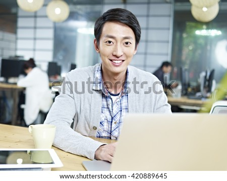 young asian businessman working in office using laptop computer. - stock photo