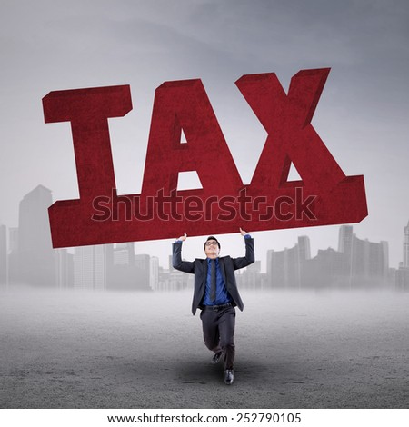 Young asian businessperson holding a tax sign outdoors on the cloudy day - stock photo