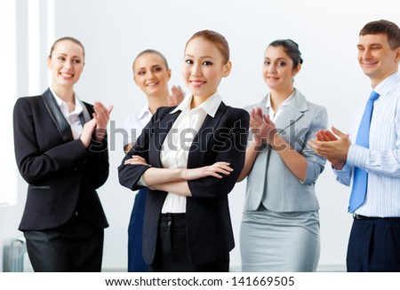 Young asian businesswoman smiling with colleagues applauding joyfully at background - stock photo