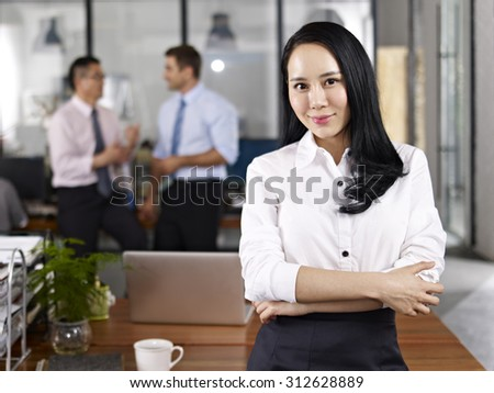 young asian businesswoman standing in office with multiethnic colleagues talking in background. - stock photo