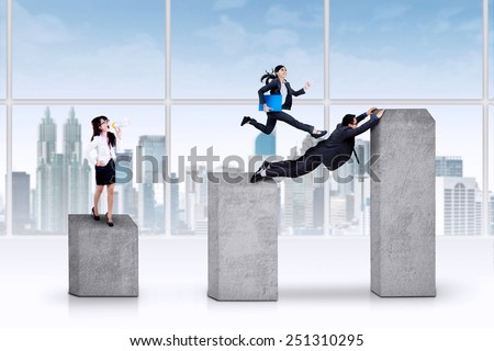 Young asian businesswoman standing on business chart and giving orders on her team - stock photo