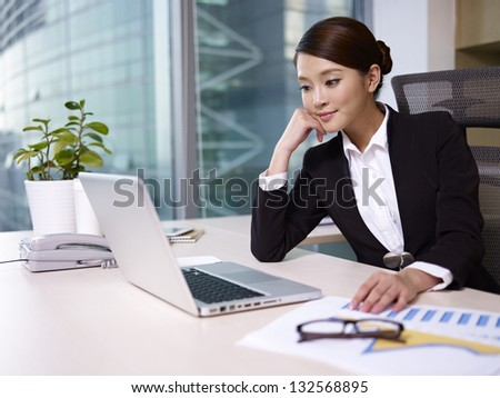 young asian businesswoman working in office. - stock photo