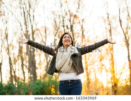Young Asian carefree woman in mid 20s with arms in the air at the park on an autumn late afternoon - stock photo