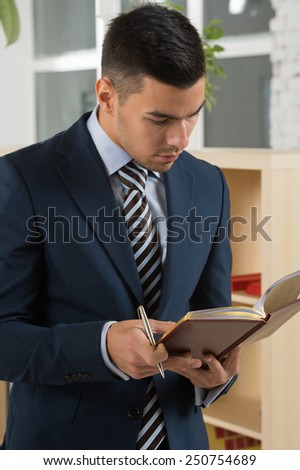 Young asian caucasian business man holding a book while planning his schedule at office - stock photo