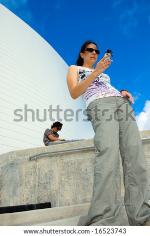 Young asian-caucasian woman sending text message while young asian-caucasian man is reading a book in the background - stock photo