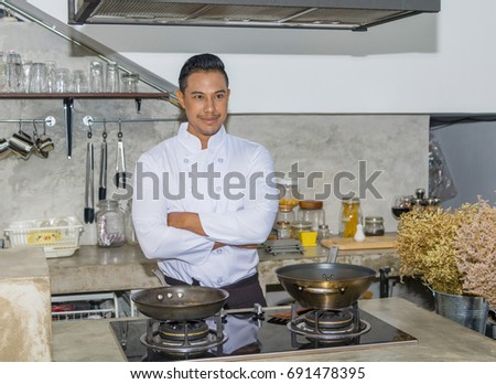 young Asian chef is cooking in the kitchen.