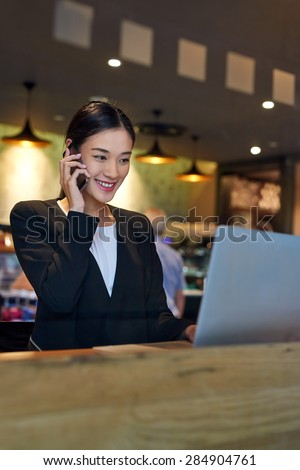 young asian chinese business woman using cafe wifi connection for laptop computer talking on mobile phone for work - stock photo