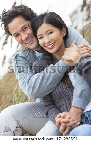Young Asian Chinese man & woman, boy & girl, couple sitting in the sand dunes on a beach - stock photo