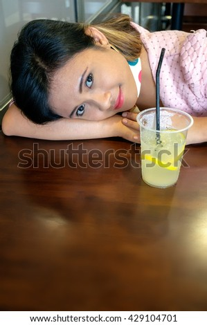 Young Asian college girl student sitting on campus cafe, smile, feel relax and enjoy - stock photo