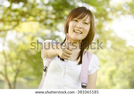 Young Asian college girl student standing on campus lawn, giving thumb up and smiling.