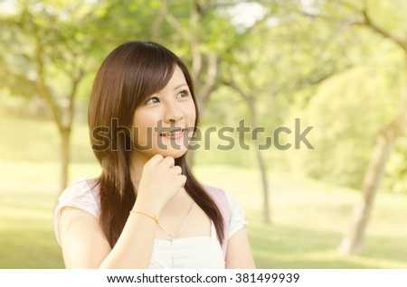 Young Asian college girl student standing on campus lawn, thinking and smiling. - stock photo