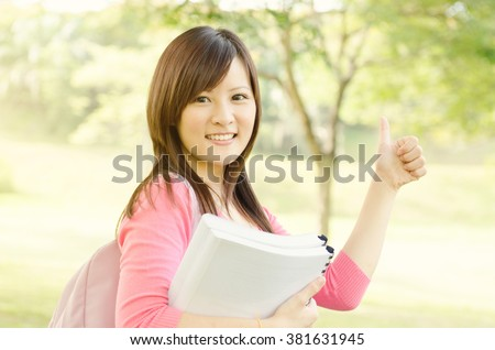 Young Asian college student on campus, holding books and giving a thumb up. - stock photo
