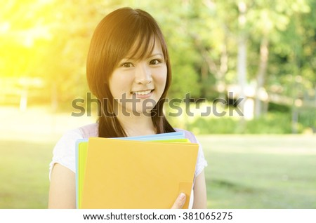 Young Asian college student standing on campus lawn, holding file folder and smiling. - stock photo