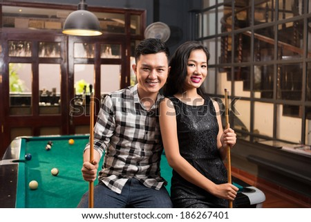 Young Asian couple holding cues sitting on the edge of the pool table - stock photo