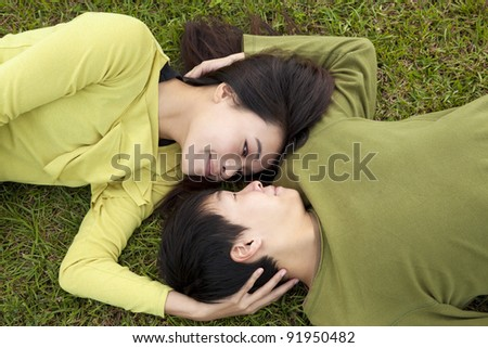 Young asian couple in love on the grass - stock photo