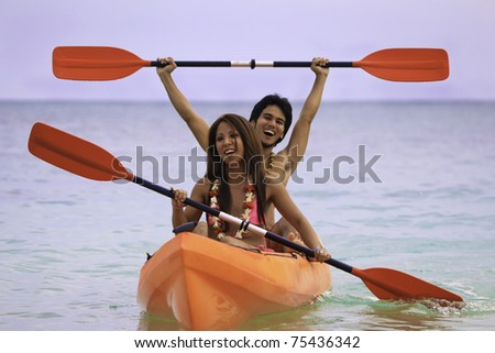 young asian couple in their kayak in hawaii - stock photo