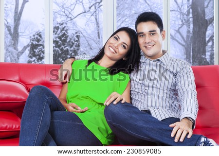 Young asian couple looking and smiling on the camera at home with winter background on the window - stock photo
