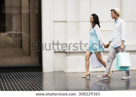 Young Asian couple on a city street after shopping - stock photo