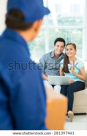 Young Asian couple receiving a purchase, ordered online - stock photo
