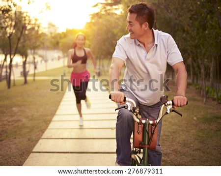 young asian couple running, riding bike outdoors in park at sunset, fitness, sport and exercise, healthy life and lifestyle concept. - stock photo