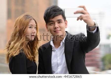 Young Asian couple taking picture outdoors