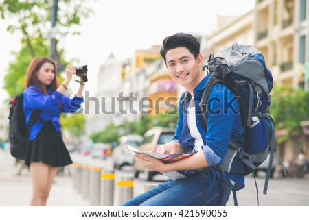 Young Asian couple travelers looking the map.  - stock photo