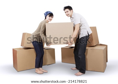 Young asian couple unpacking cardboard in new home - stock photo