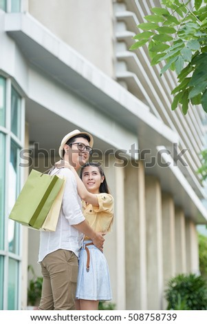 Young Asian couple with shopping bags hugging outdoors