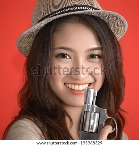 Young asian cute woman with handgun revolver - stock photo