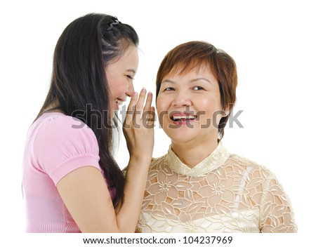 Young Asian daughter talking secretly to her mum - stock photo