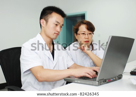 young asian doctor and nurse working with laptop - stock photo