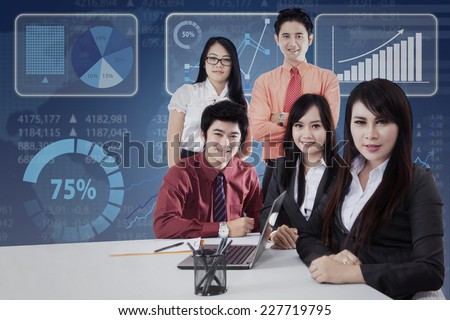 Young asian entrepreneurs in the business meeting and smiling on camera - stock photo
