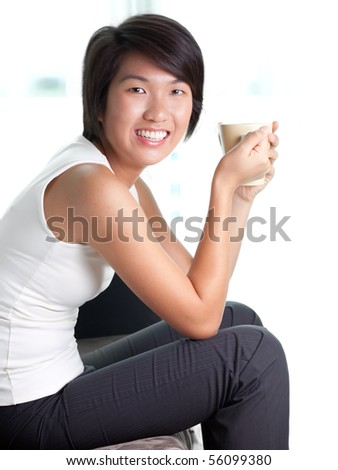 Young Asian executive--Chinese/Japanese ethnicity--relaxing on her couch at home with a cup of coffee after work. In semi-formals without coat.