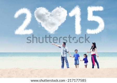 Young asian family holding hands and walking at beach under cloud of 2015 - stock photo