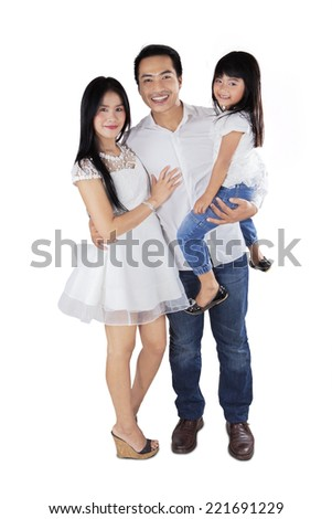 Young asian family standing in studio and smiling at camera - stock photo
