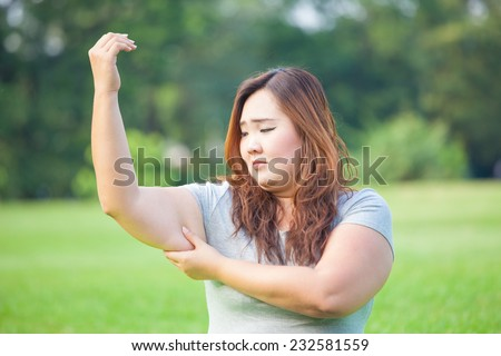 Young asian fat woman checking her arm fat - stock photo